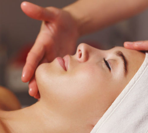 Spa treatment. Face massage. Massage of the forehead and chin zone of the client.