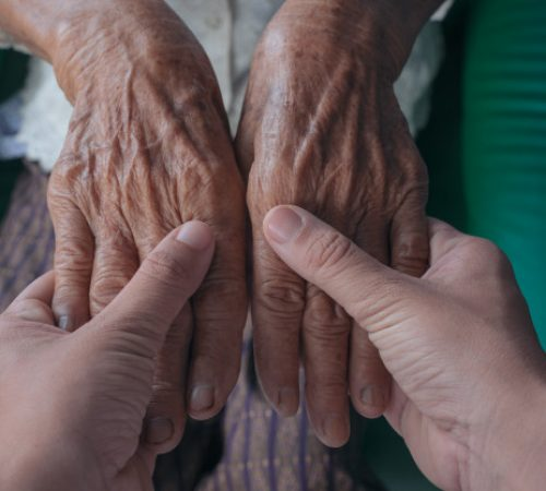 young-woman-holding-elderly-woman-s-hand_1150-12496